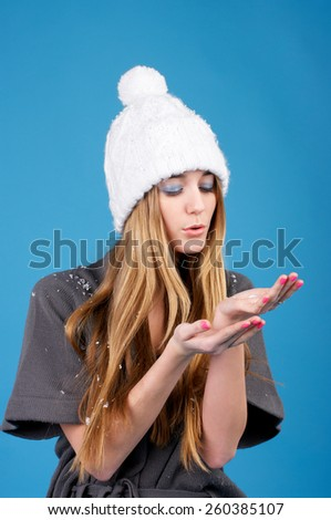 Young beautiful woman in white winter hat over blue background