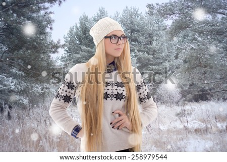 young beautiful woman in winter clothes walking in forest - stock photo