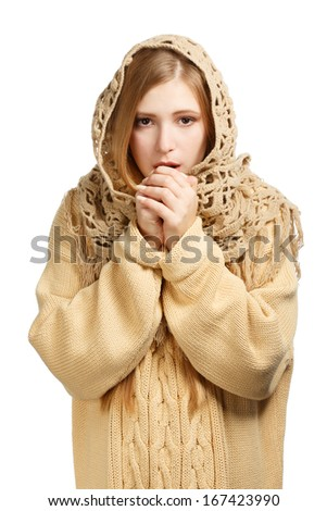 Young beautiful woman in woollen comforter and knitted sweater breathing to warm frozen hands isolated on white background - stock photo