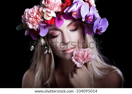 young beautiful woman in wreath of flowers presses flower to her lips, black background - stock photo