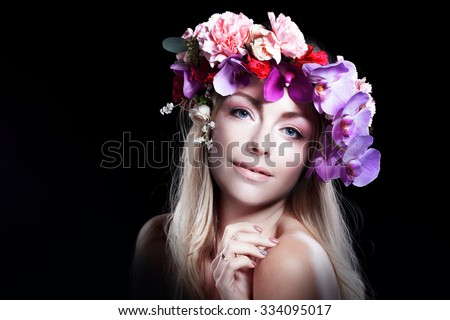 young beautiful woman in wreath of flowers smiles and looks into the camera, black background