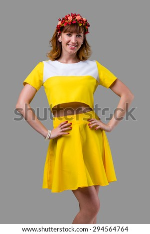 Young beautiful woman in yellow dress with red wreath on her head, isolated on gray - stock photo