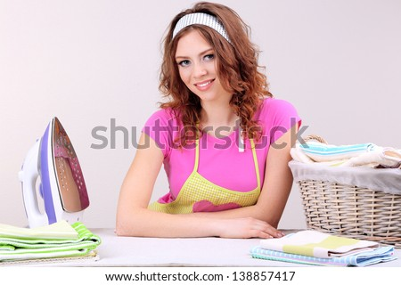 Young beautiful woman ironing clothes in room on grey background