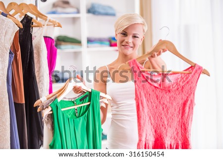 Young beautiful woman is choosing between two dress in the store.