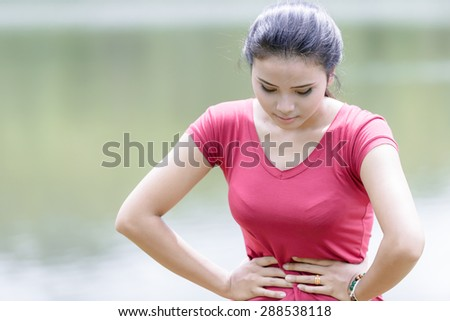 Young beautiful woman is having stomach ache on nature background - stock photo