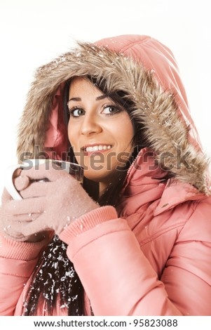 Young beautiful woman is holding cup with tea on a cold winter day