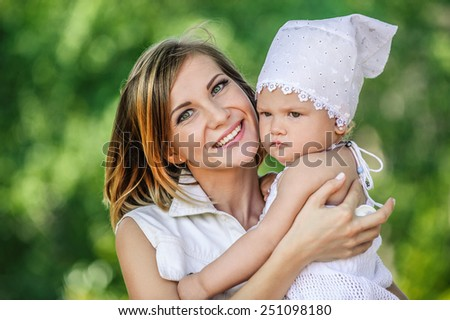 Young beautiful woman is holding her little daughter, against summer city park. - stock photo
