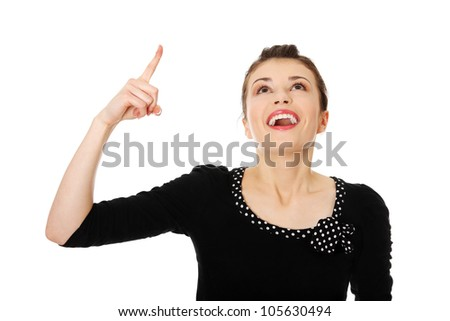 Young beautiful woman is laughing and pointing up. Isolated on the white background.