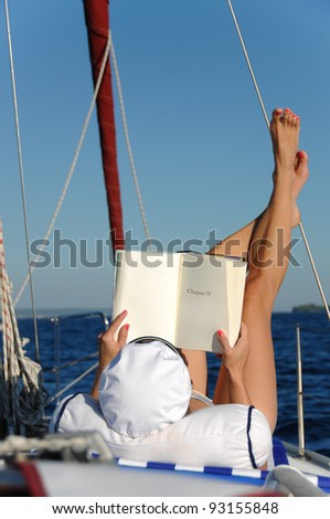 Young beautiful woman is relaxing and sunbathing while reading a book on a sailboat in the open adriatic sea. Book can be used as copy space for small alterations. - stock photo