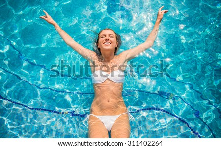 Young beautiful woman is relaxing in swimming pool. - stock photo