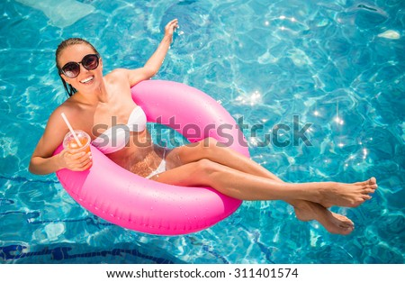 Young beautiful woman is relaxing in swimming pool with rubber ring and cocktail. - stock photo