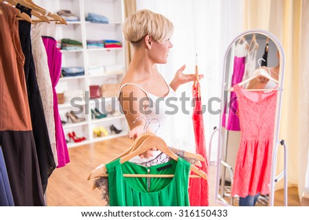 Young beautiful woman is trying dresses in front of mirror in room.