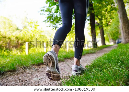 Young beautiful  woman jogging in summer park. Woman in sport outdoors health concept - stock photo