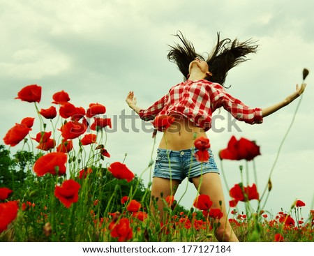 Young beautiful woman jumping and dancing through a poppy field, summer outdoor. Toned, noise added. - stock photo