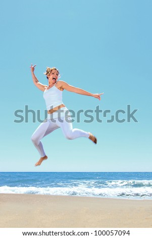 young beautiful woman jumping on the beach