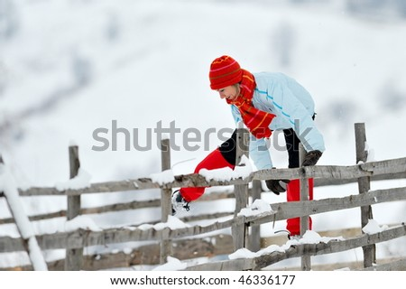 young beautiful woman jumping over fence