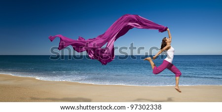 Young beautiful woman jumping with a violet tissure in the beach - stock photo