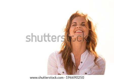 Young beautiful woman laughing outdoor with sun in her back