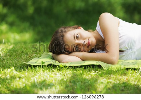 Young beautiful woman laying on the grass