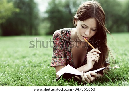 Young beautiful woman lays on a grass in park with a diary in hands