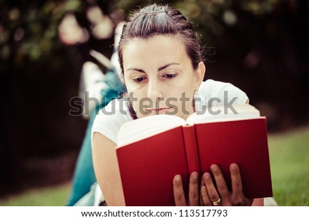Young beautiful woman lays on green field and reads book, Italy