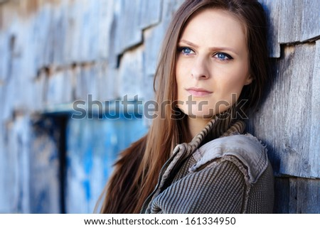 Young beautiful woman leaning on a cabin log with a pensive attitude - stock photo