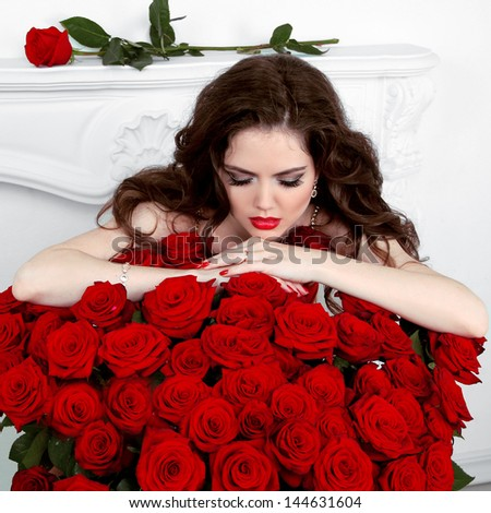 Young beautiful woman leaning on the red roses bouquet. Valentines day - stock photo