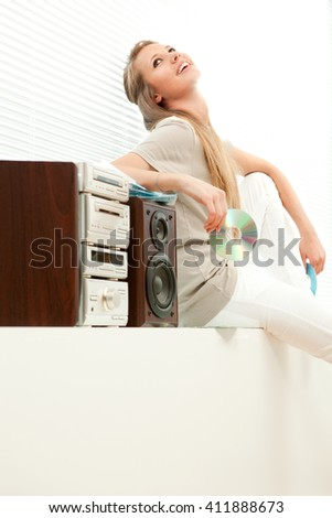 Young beautiful woman listen music with cd rom in a living room