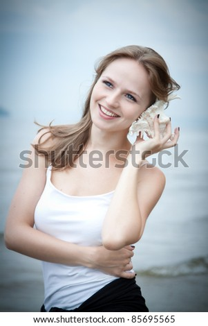 Young beautiful woman  listening  to a seashell