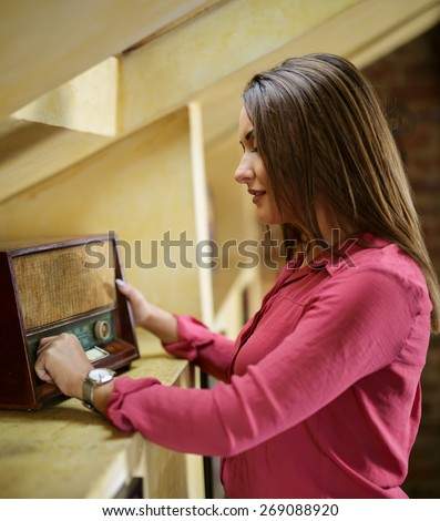 Young beautiful woman listening to an old radio - stock photo