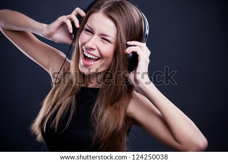 young beautiful woman listening to music on headphones enjoying a dance
