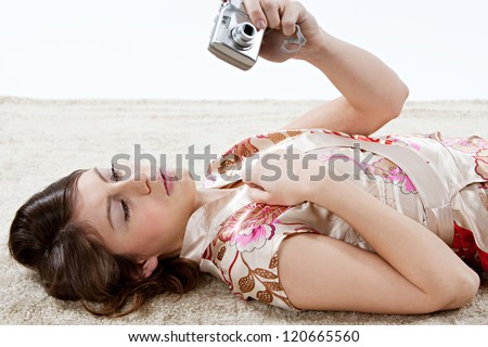 Young beautiful woman looking at a digital photo camera while laying down on a furry carpet at home against a white background. - stock photo