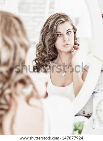 Young beautiful woman looking at her face in the mirror - stock photo
