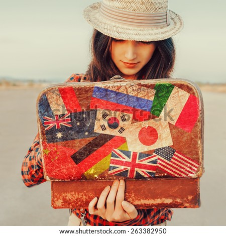 Young beautiful woman looking for something in the open suitcase. Suitcase with stamps flags of different countries. Concept of travel - stock photo