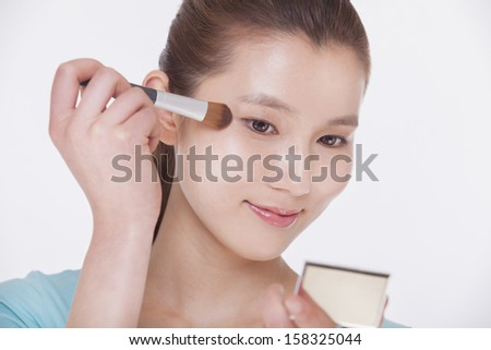 Young beautiful woman looking into a mirror and applying make up  - stock photo