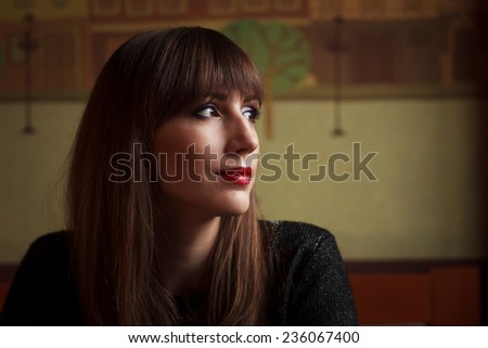 Young beautiful woman looking into window in restaurant. Dreaming girl in cafe - stock photo