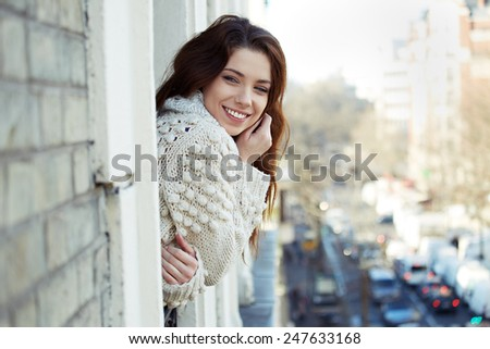 Young beautiful woman looks out the window at the city