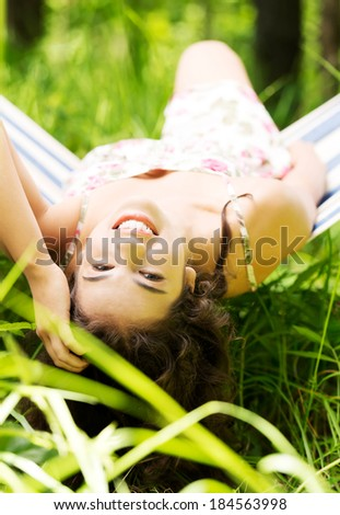 Young beautiful woman lying and relaxing in a hammock over sunny day. - stock photo