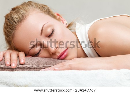 Young beautiful woman lying down on a bed in bedroom