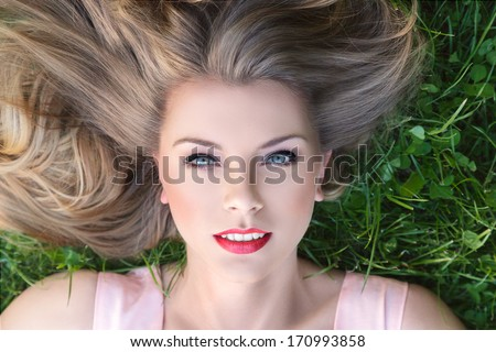 Young beautiful woman lying down on a grass - stock photo