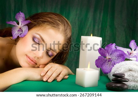 Young beautiful woman lying down with orchids - stock photo
