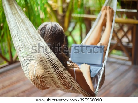 Young beautiful woman lying in a hammock with laptop in a tropical resort. back view. - stock photo