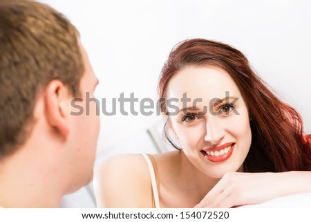 young beautiful woman lying in bed and looking at the camera - stock photo