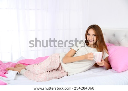 Young beautiful woman lying in bed with cup of hot drink - stock photo