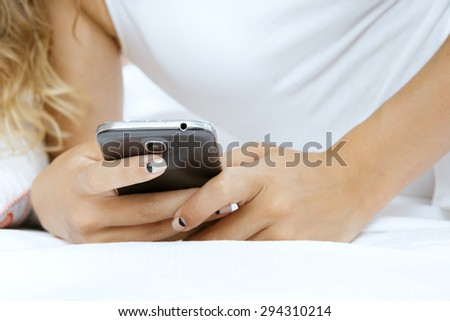 Young beautiful woman lying in bed with her phone at home - stock photo