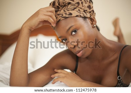 Young beautiful woman lying on a bed in a luxury hotel room - stock photo