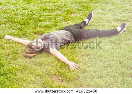 Young beautiful woman lying on grass with arms wide open and listening music on headphones on sunny day - stock photo