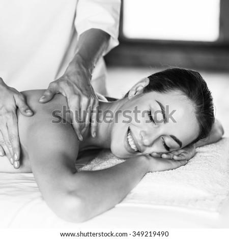Young beautiful woman lying on massage table and enjoying massage. - stock photo