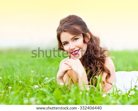 Young beautiful woman lying on the grass and smiling - stock photo