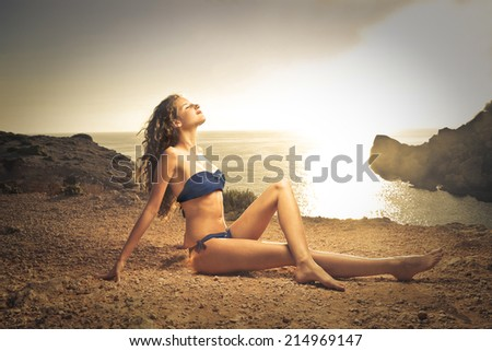 young beautiful woman lying on the rocks at the sunset